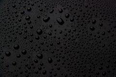 Droppar av vatten på en svart bakgrund royaltyfria foton