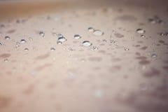 Droppar av vatten på ett beige tyg Royaltyfria Bilder