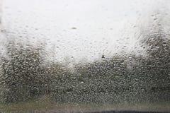Droppar av vatten på vindrutan av en bil arkivfoto