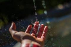 Droppar av vatten som slår fingret royaltyfri foto
