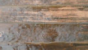 Droppar av vattentakten mot en träyttersida långsam rörelse arkivfilmer