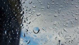Droppar för regnvatten på blått Fotografering för Bildbyråer