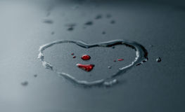 Droppar och hjärta för rött vatten formar på mörk bakgrund, mjuk fokus Royaltyfri Fotografi