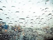 Droppar på bilvindrutan på regnet på vägen Arkivfoto