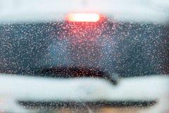 droppar på vindrutan av bilen i asken en suddig vit bil på bakgrund royaltyfri bild