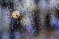 Droppar reflekterade i fönstret med färgrika reflexioner arkivbild