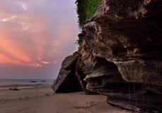 Droppe av den steniga kusten för Dan skärm solnedgångglödet Royaltyfri Bild