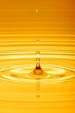 Droppe av vatten i guld royaltyfri fotografi