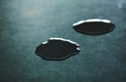 Droppe av vattenrullningen på svart tegelplattaräknare Arkivfoto