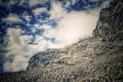 Droppe för brant klippa från ett berg med djupblå himmel och moln arkivbild
