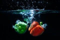 Droppe för söt peppar in i vatten på svart bakgrund. Royaltyfria Foton
