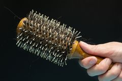 Dropped curls of hair on a comb in a hand on a black background, concept royalty free stock photography