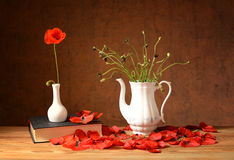 Dropped flowers with the red poppies, books and a vase Stock Photography