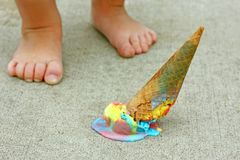 Dropped Ice Cream Cone by Child's Feet. A dropped rainbow colored ice cream cone lays upside down on the sidewalk at the feet of a young child royalty free stock image