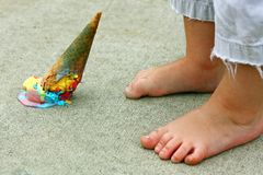 Dropped Ice Cream Cone by Feet. A dropped rainbow colored ice cream cone lays upside down on the sidewalk at the feet of a young child royalty free stock image
