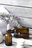 A dropper bottle of lavender essential oil. Closeup. A dropper bottle with lavender essential oil on a old wooden surface. Lavender twig and white towels in the stock photos