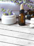 A dropper bottle of lavender essential oil. Closeup. A dropper bottle with lavender essential oil on a old wooden surface. Lavender twig and white towels in the royalty free stock photo