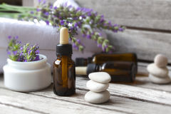 A dropper bottle of lavender essential oil. Closeup. A dropper bottle with lavender essential oil on a old wooden surface. Lavender twig and white towels in the stock image