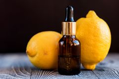 Dropper bottle of lemon essential oil. A dropper bottle of lemon essential oil. Lemons on the wooden rustic background stock image