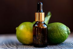 Dropper bottle of lime essential oil. A dropper bottle of lime essential oil. Limes on the wooden rustic background stock images