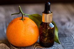 Dropper bottle of mandarin essential oil. A dropper bottle of mandarin essential oil. Mandarins on the wooden rustic background royalty free stock photos
