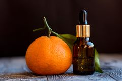 Dropper bottle of mandarin essential oil. A dropper bottle of mandarin essential oil. Mandarins on the wooden rustic background stock photos