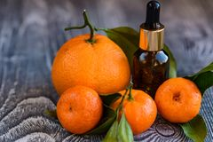 Dropper bottle of mandarin essential oil. A dropper bottle of mandarin essential oil. Mandarins on the wooden rustic background royalty free stock photography