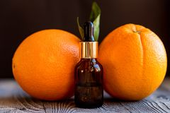 Dropper bottle of orange essential oil. A dropper bottle of orange essential oil. Oranges on the wooden rustic background stock images