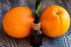 Dropper bottle of orange essential oil. A dropper bottle of orange essential oil. Oranges on the wooden rustic background stock image