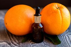 Dropper bottle of orange essential oil. A dropper bottle of orange essential oil. Oranges on the wooden rustic background stock photography