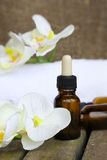 Dropper bottles pure orchid essential oil. Closeup. A dropper bottle of organic orchid pure oil on a wooden surface. White towels, artificial orchid heads,rives Royalty Free Stock Images