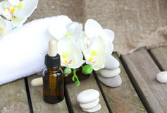 Dropper bottles pure orchid essential oil. Closeup. A dropper bottle of organic orchid pure oil on a wooden surface. White towels, artificial orchid heads,rives Stock Photos