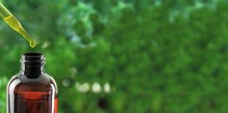 Droppglass över den nödvändiga olje- flaskan arkivbild