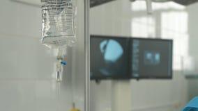 Droppglass mot medicinsk bildskärm i sjukhuskirurgirum stock video