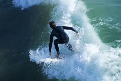 Dropping in. Young man with wetsuit surfing on a wave Royalty Free Stock Photo