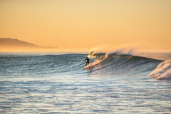 Dropping in on Autumn morning surf session. Stock Photography