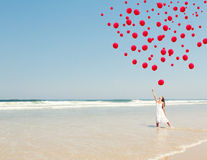 Dropping ballons in the sky. Beautiful girl in the beach dropping red ballons in the sky stock images