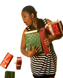 Dropping christmas presents. Young african girl dropping a few christmas presents royalty free stock photo