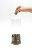 Dropping coin into glass jar Stock Images