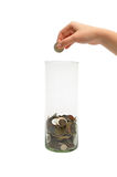 Dropping coin into glass jar Royalty Free Stock Images
