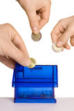 Dropping coins. Human hands dropping money in coin bank Royalty Free Stock Images