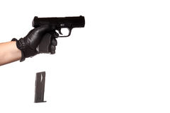 Dropping a Handgun Clip. A man reloading a weapon drops the clip from a black handgun. Slight motion blur on the falling ammunition clip Royalty Free Stock Images