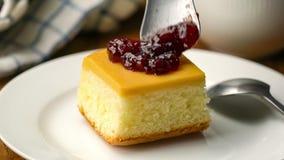 Dropping jam onto a piece of cake on ceramic dish.