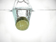Dropping lime in water Stock Image
