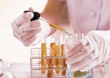 Dropping liquid to test tubes stock photography