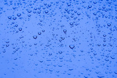 Drops. Water droplets on the glass window with blue sky background Royalty Free Stock Photo