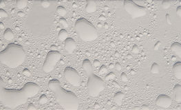 Drops. The drops of water on the white painted surface Royalty Free Stock Image