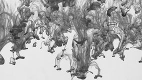Drops of black paint flowing from top to bottom under water. stock footage