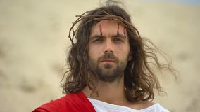 Drops of blood running down Jesus face, God looking on camera, crucifixion
