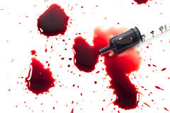 Drops of blood and a syringe Stock Images